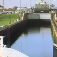 Panama Canal Transit - Preparing to enter the first lock, behind a cargo ship.