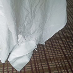 Torn and frayed sheet on bed